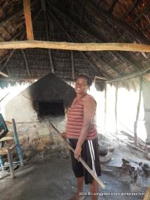 Proud Madan Ti Pousie next to her furnace